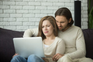 young couple looking at computer monitor and upset about online scam